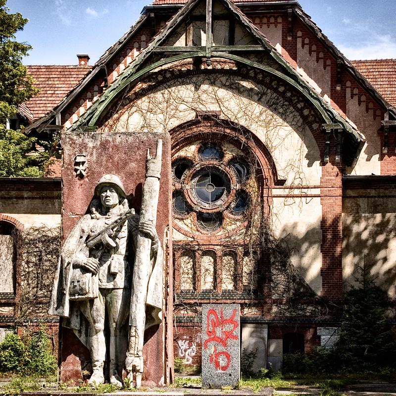 Aussenansicht des Männerbereiches in den Beelitzer Heilstätten mit einem russischen Denkmal im Vordegrund